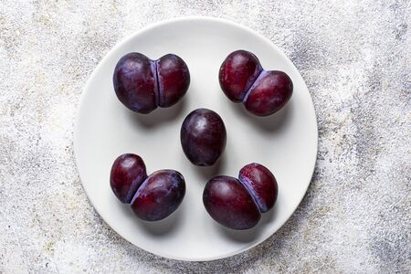 Oddly shaped and normal plums. Abnormal organic fruit