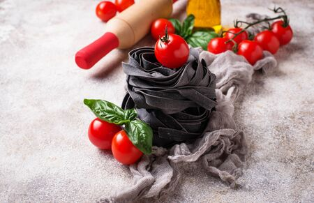 Black uncooked pasta with tomato and basil Foto de archivo - 129758655