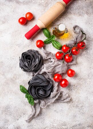 Black uncooked pasta with tomato and basil Foto de archivo - 129758684