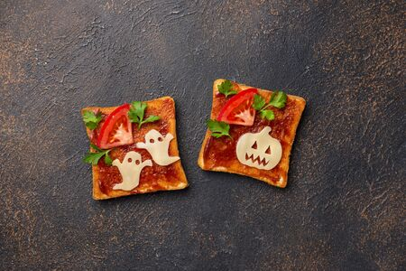 Halloween sandwiches toasts with ghost and pumpkin from cheese