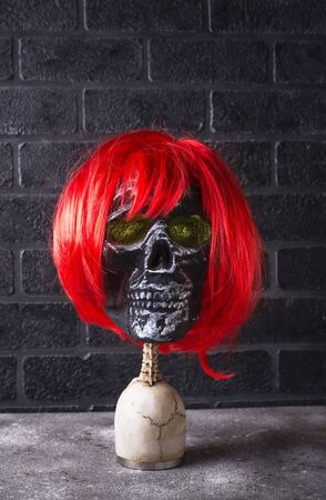 Human skull with red wig. Funny Halloween idea
