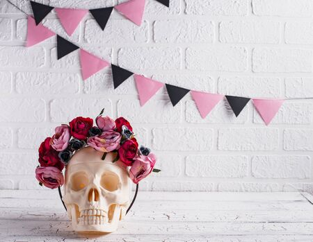 Skull with wreath of pink flowers. Halloween creative decor