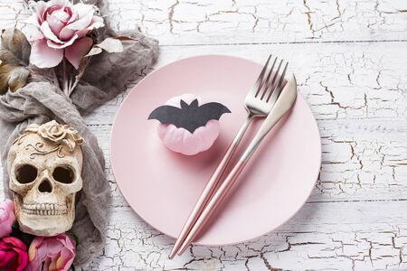 Halloween table setting in pink colors with skull
