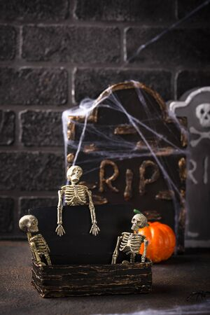Halloween background with skeletons, tomb and pumpkin