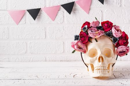 Skull with wreath of pink flowers. Halloween creative decor