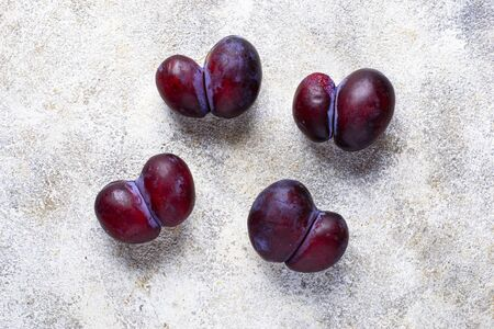 Ugly plums. Abnormal organic conjoined fruit in shape of heart or butterfly 版權商用圖片