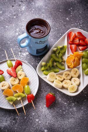 Chocolate fondue with fruits. Sweet summer dessert