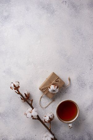 Composition with cotton branch, gift box and tea.