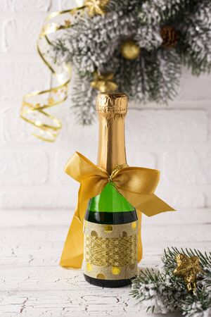 Bottle of champagne in a gold wrapper with a bow. Christmas or New year gift idea