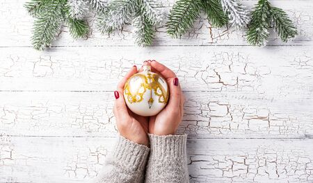 Festive background with golden Christmas tree ball in hand