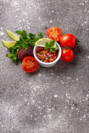 Traditional mexican tomato salsa sauce on wooden background Imagens