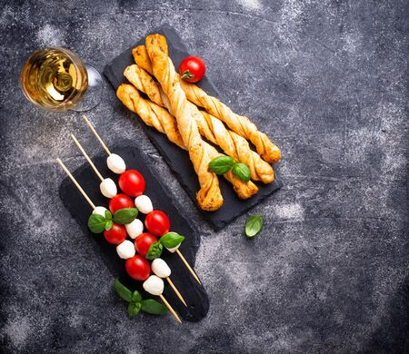 Traditional Italian antipasto caprese skewers and grissini bread