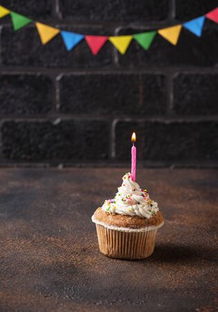 Birthday cupcake with cream and candle on brick wall background