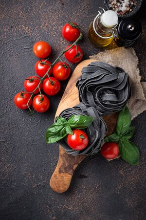 Black uncooked pasta with tomato and basil Banque d'images