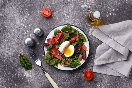 Healthy salad with prosciutto, tomato, green leaves and egg