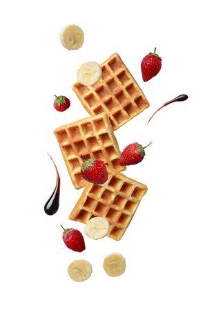 Waffles belgas con fresas y plátano. Levitación de alimentos. Aislado en blanco