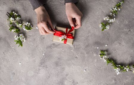 Woman hand hold gifts boxes. Background with cherry blossom Zdjęcie Seryjne