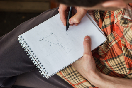 wrote: the young man wrote mathematical formulas in the notebook