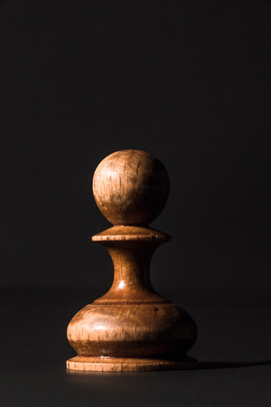 battle plan: chess pieces made out of wood on a black background Stock Photo