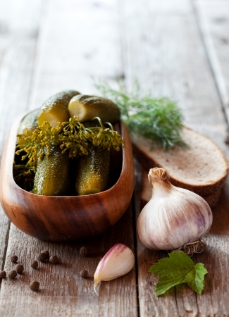 Salted cucumbers on wooden background with garlic photo