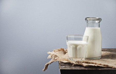 Milk in a glass bottle on wooden background