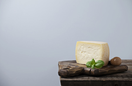 hard cheese: Hard cheese on wooden board with basil leaf