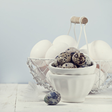 Hen and quail eggs on wooden background