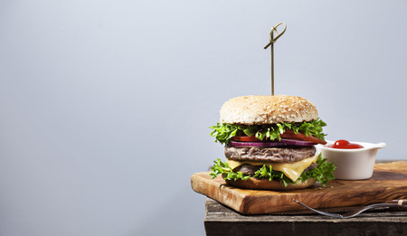 Burger on wooden board with tomato sauce Stock Photo
