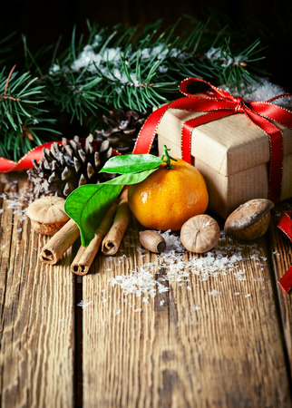 Composition with tangerines, gift, pine cones and spruce