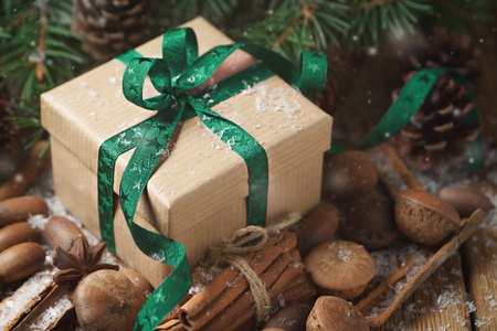 Gift with a green ribbon, cinnamon, pine cones and spruce branches Stock Photo - 69658429