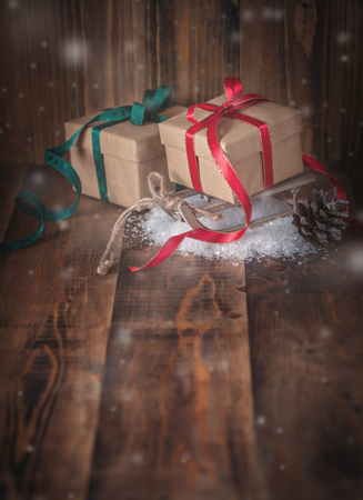 Two wrapped gifts with ribbons on wooden background
