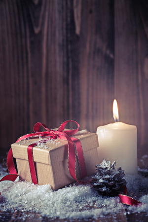 Christmas composition with a gift and a candle on wooden background Stock Photo