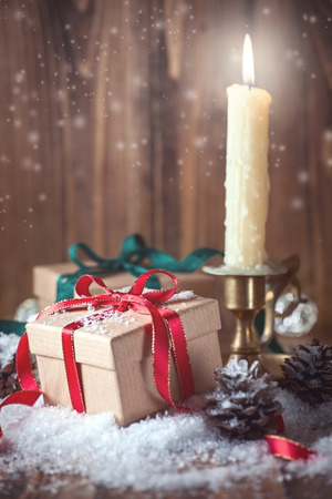 Christmas composition with gifts and a candle on wooden background Stock Photo - 69689702
