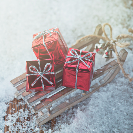 Christmas background with pile of gifts placed on wooden sledge in snow.
