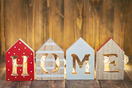 Word HOME made of wooden letters with christmas lights behind