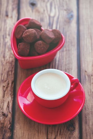 Red cup and chocolate candies on wooden background Stock Photo