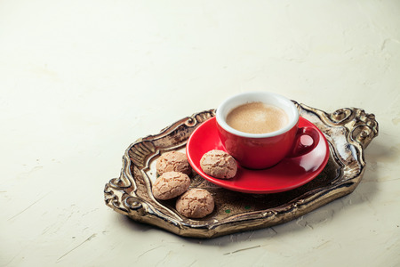 Fresh coffee in a red cup with traditional almond cookies