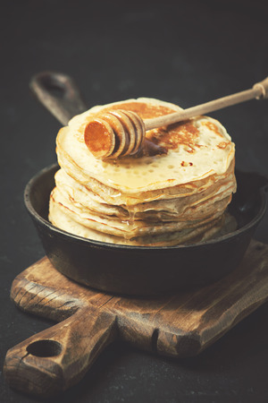 Pancakes in a cast iron skillet on dark background Stock Photo