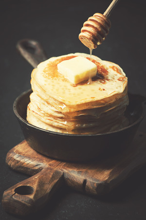 Pancakes in a cast iron skillet on dark background