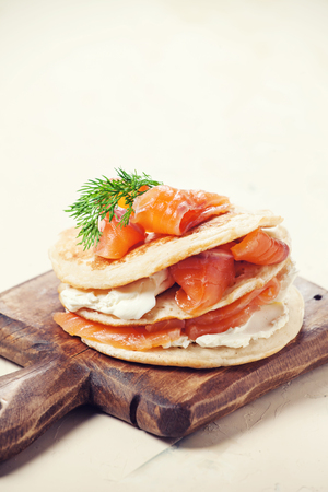 Pancakes with salmon and cream cheese on wooden board Stock Photo - 73346977