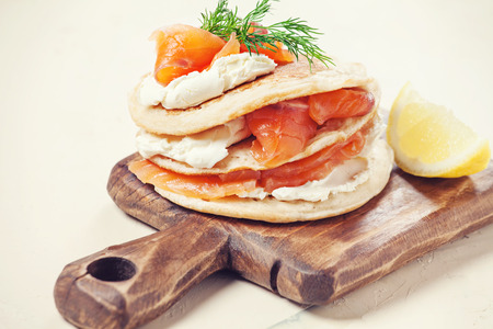 Pancakes with salmon and cream cheese on wooden board