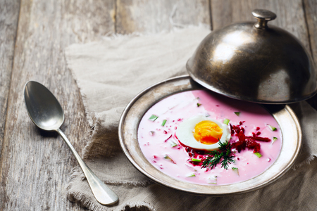 Cold beetroot soup on wooden background