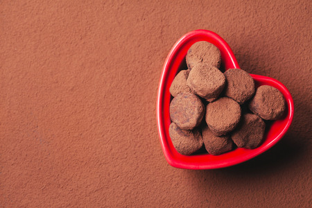 Chocolate truffles in a heart shaped bowl on cocoa background