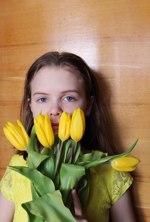 girl with gray eyes: Teen Girl with yellow tulips. Portrait photo on the wood background