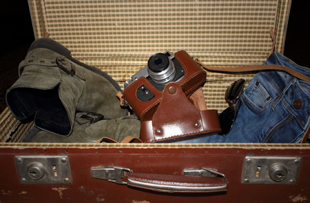 unexplored: Old suitcase with boots camera jeans and sunglass Stock Photo