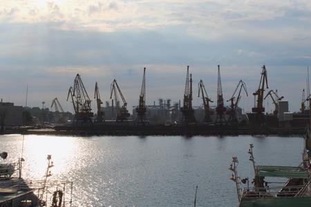 Silhouettes of big harbor cranes in the sea harbor with amazing sunlight