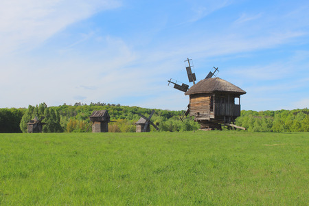 afield: Old wooden Windmill on the green meadow Countryside landscape Stock Photo