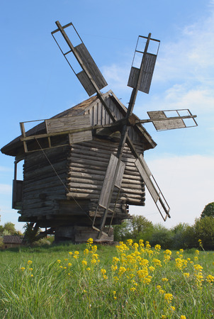 afield: Old wooden Windmill and yellow flowers Stock Photo