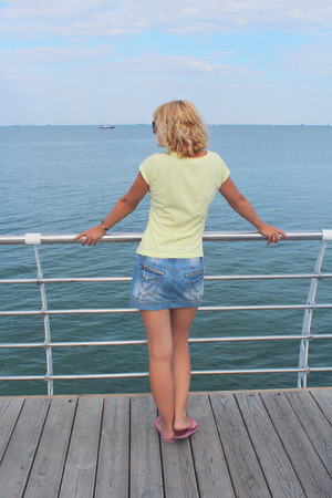 staying: Pretty Lady staying on the embankment back to us looking to the Sea Stock Photo