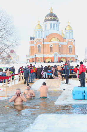 baptizing: The Day of Holy Manifestation, Dnipro river, Kiev, Ukraine, January 19, 2016. Many unidentified people plunging into ice water. Old Ukrainian tradition. Air temperature -7C 19,4F. Editorial. Editorial